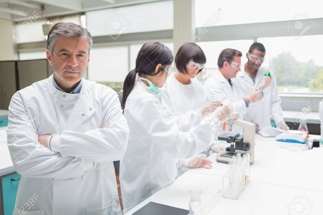 Chemist standing with arms folded in busy lab Stock Photo - 15590749