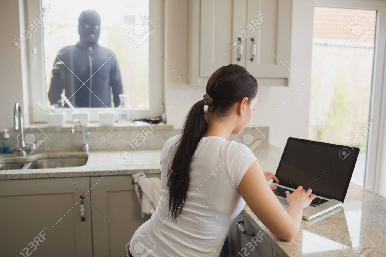 16054232-robber-looking-at-woman-in-kitchen-using-laptop-through-window.jpg