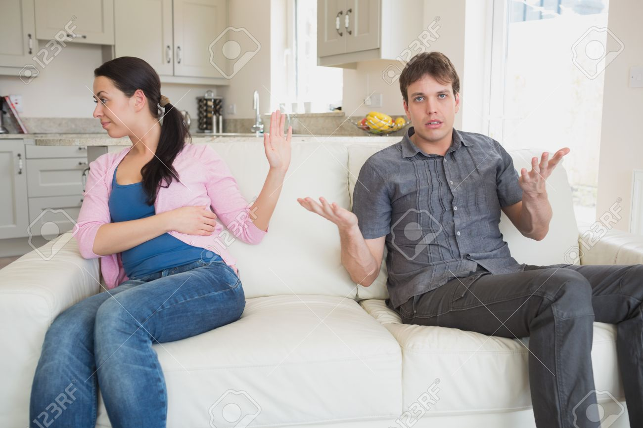 Two People Sitting On The Couch In The Living Room While Waving ...