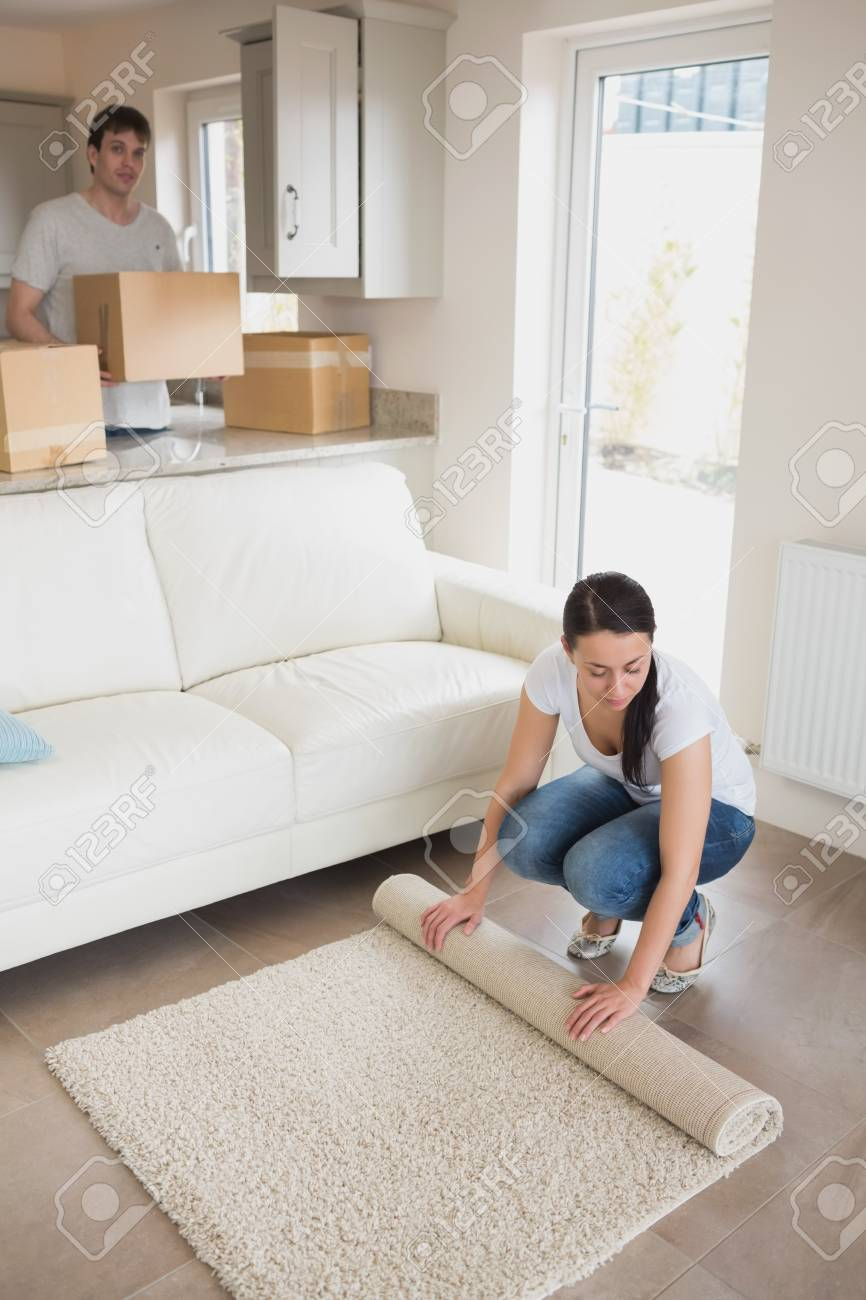Woman laying out rug with man holding moving boxes in living room Stock Photo - 16055117