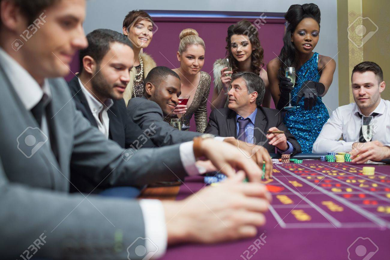 women watching men play roulette in casino stock photo picture stock photo women watching men play roulette in casino