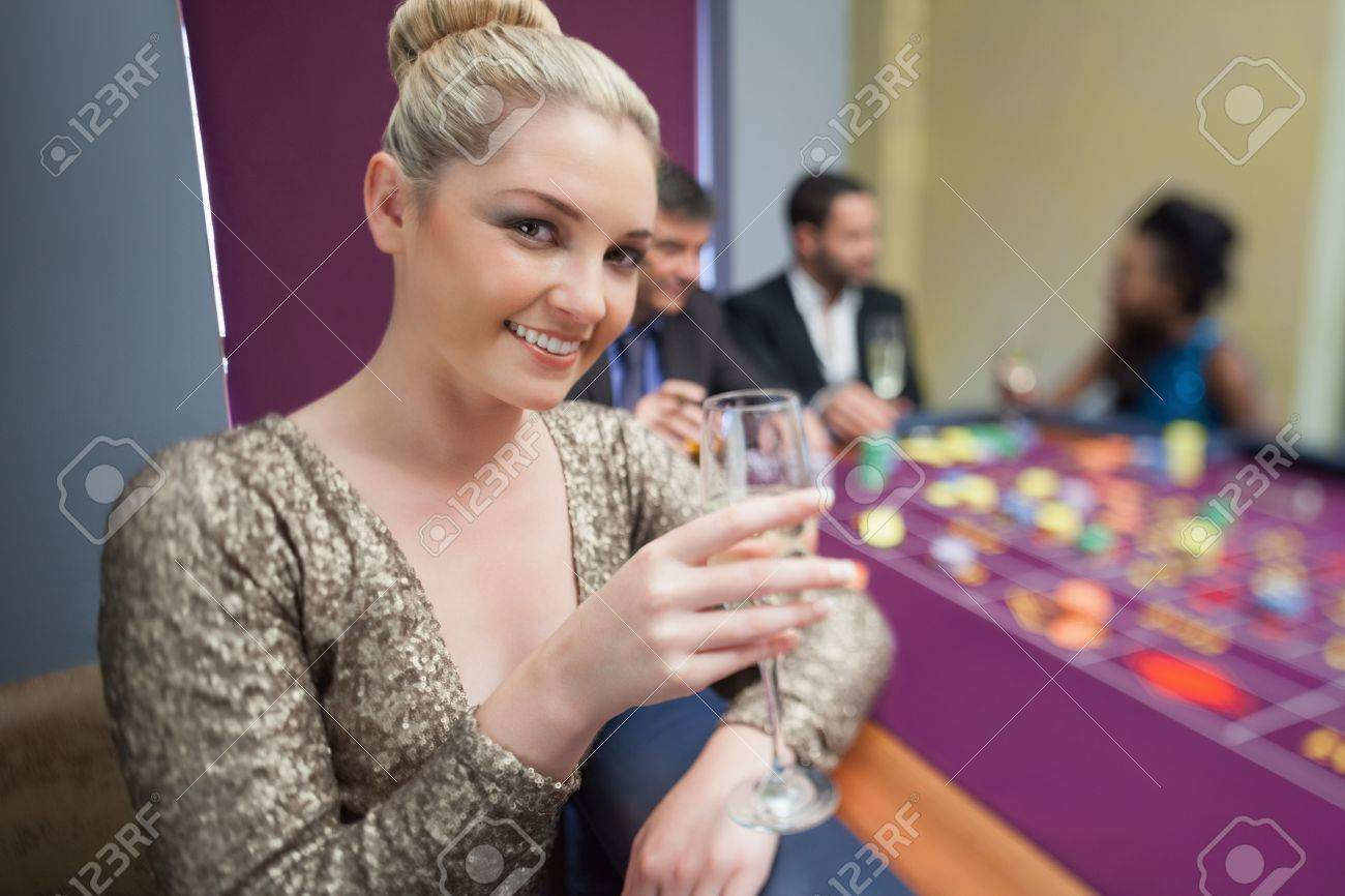 Blonde lifting champagne glass at roulette table in casino Stock Photo - 16076637