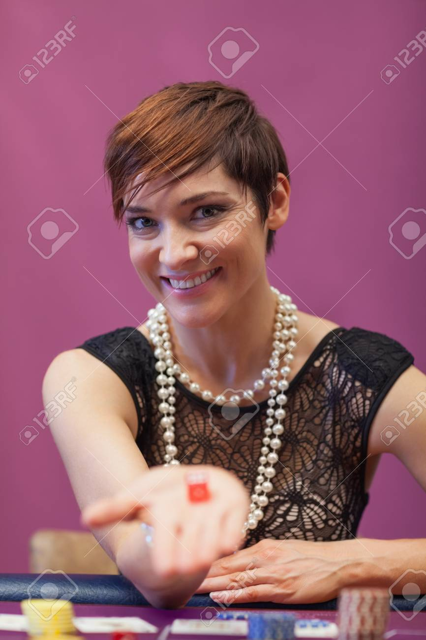 Woman sitting in a casino at table while holding dices and smiling Stock Photo - 16075572