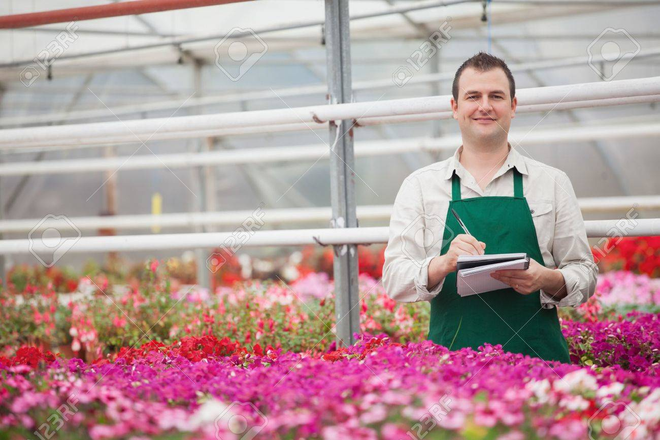 Smiling man taking notes in the greenhouse in garden center Stock Photo - 16066076