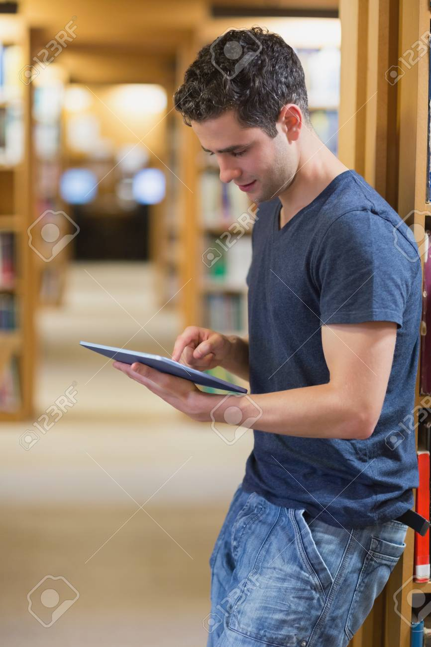 College girl using tablet pc with blurred students in park stock.