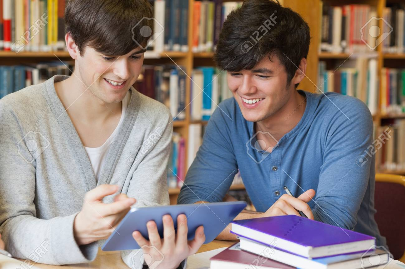 Man leaning against book shelf using tablet pc in college library.