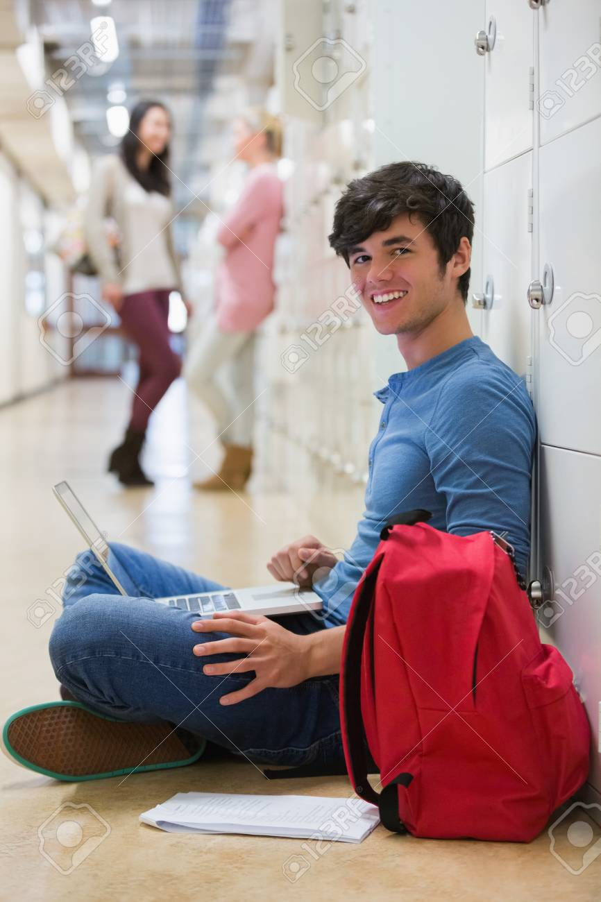 Man sitting on the floor at the hallway holding a laptop while smiling Stock Photo - 16078396