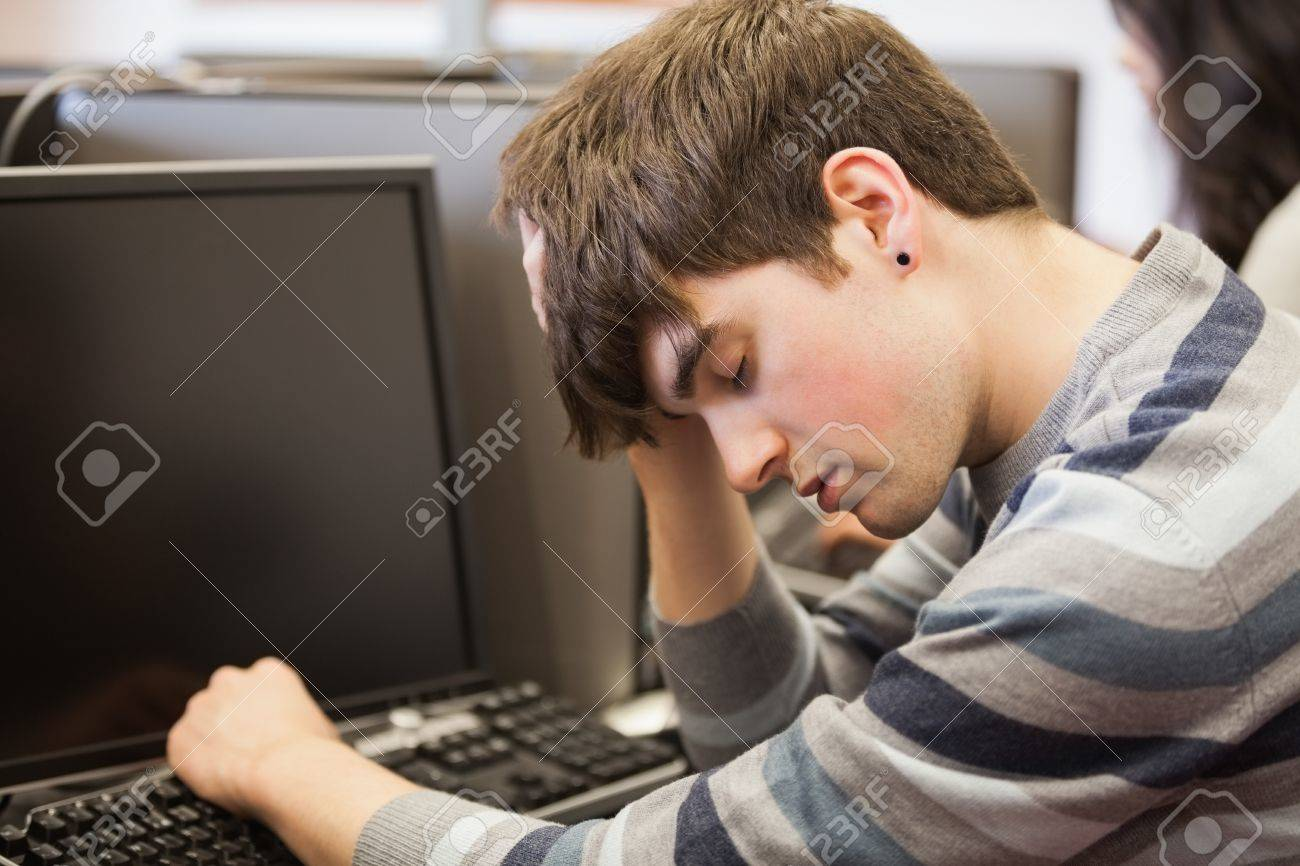 Student sitting sleeping at the computer desk in college Stock Photo - 16076941