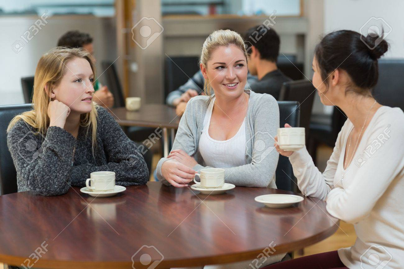 Students talking together in college coffee shop and smiling Stock Photo - 16079592