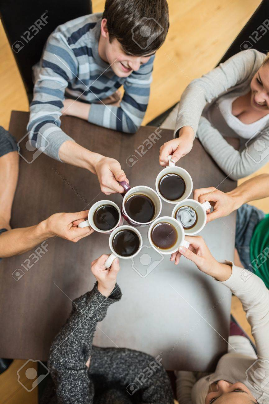 Students sitting holding cups of coffee smiling in college cafe Stock Photo - 16079225