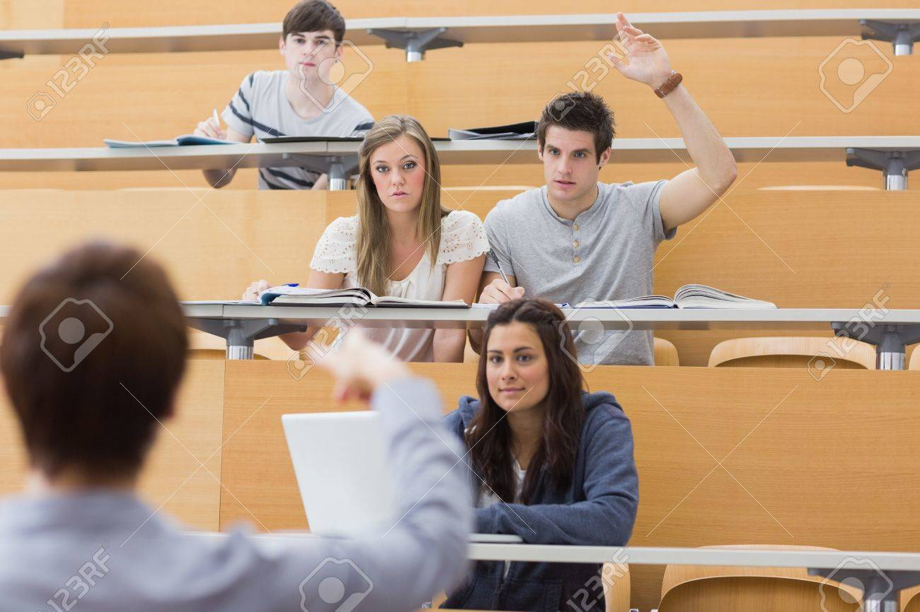 Students sitting at the lecture hall with man raising hand to ask question and lecturer is pointing at him Stock Photo - 16078563
