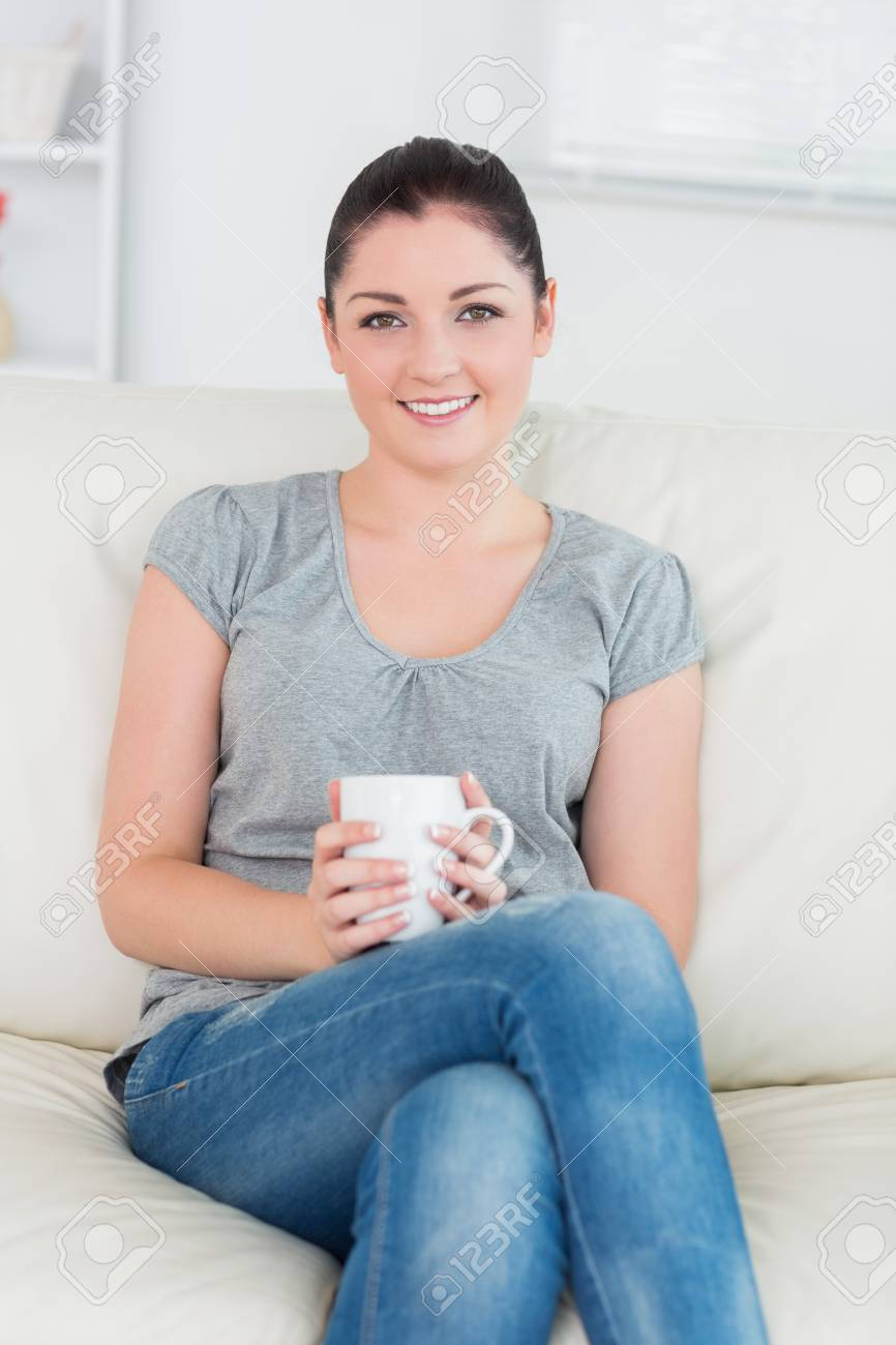 Young smiling woman sitting on the couch in a living room and holding a mug Stock Photo - 16064673