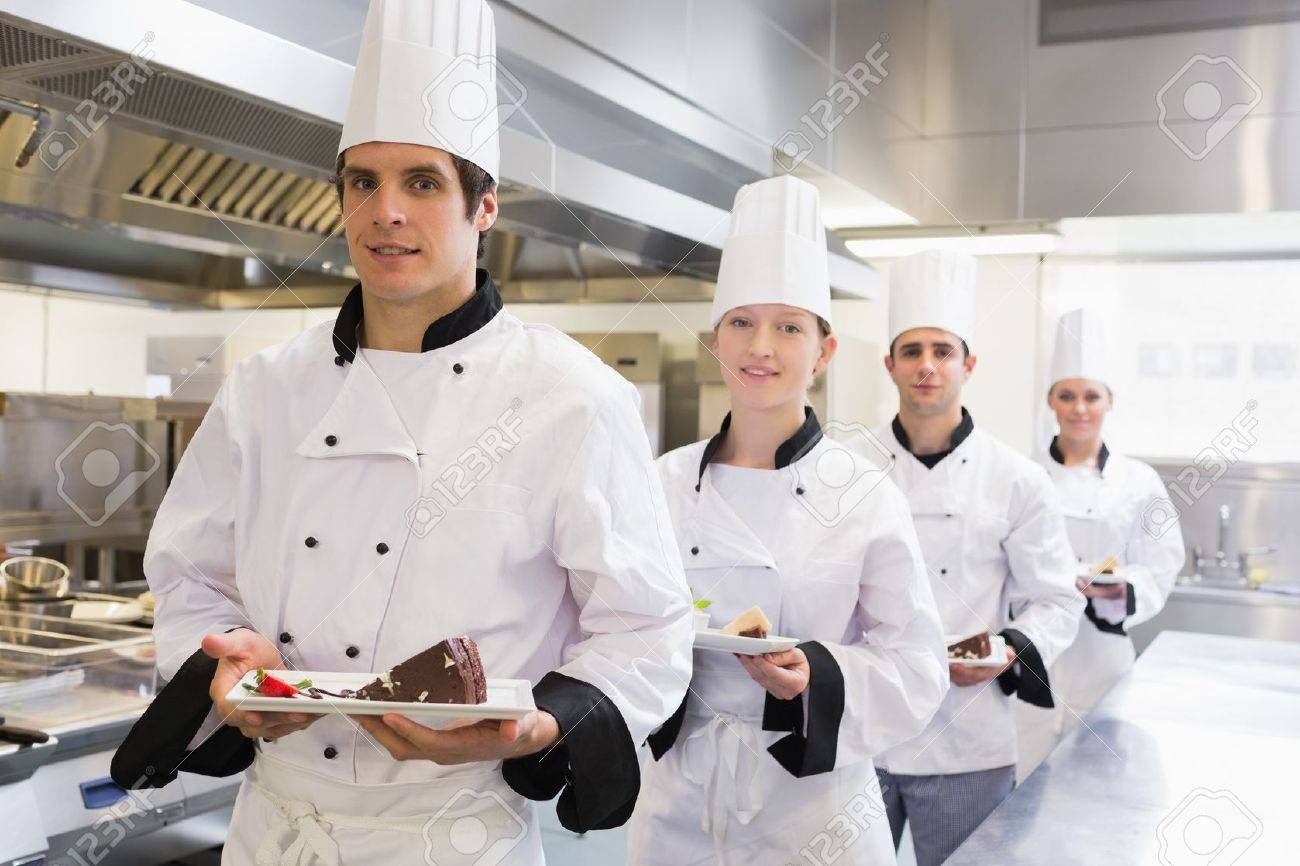 chef's team bringing the dessert in the kitchen stock photo
