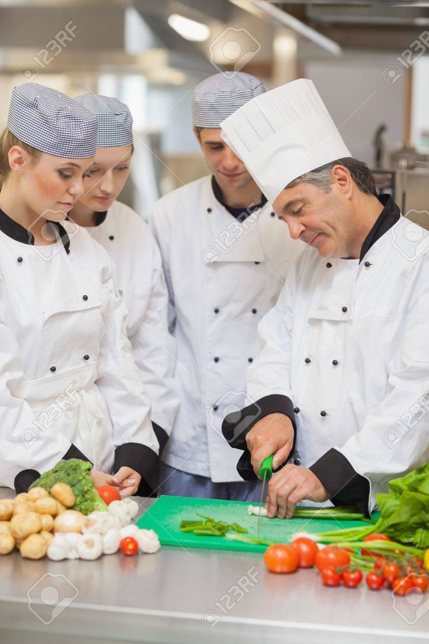Chef Teaching Cutting Vegetables To Three Trainees In The Kitchen ...