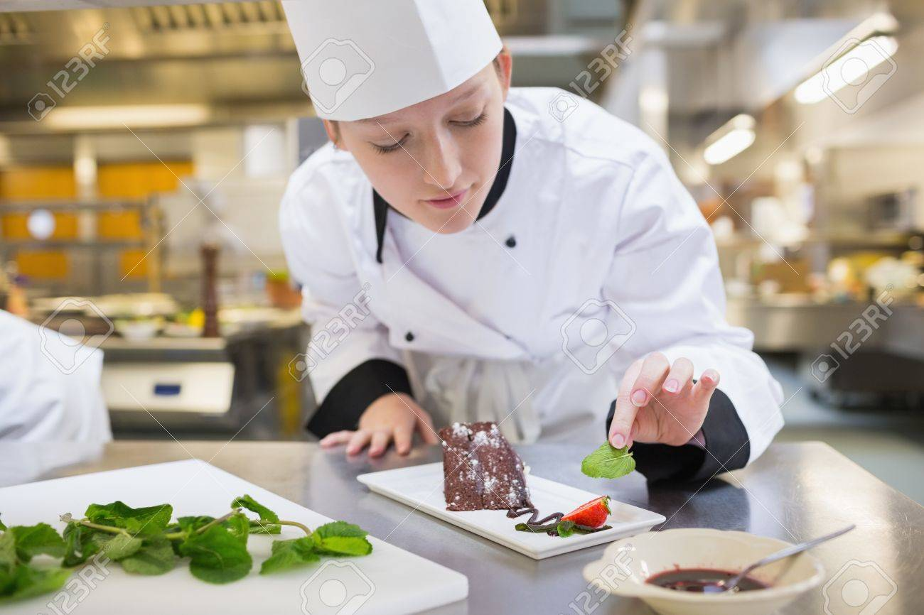 Chef Kitchen Chef Putting Mint With Her Chocolate Cake In The Kitchen Stock