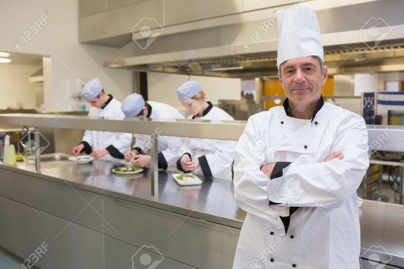 busy kitchen. Head Chef Smiling In Busy Kitchen With Team Working Behind Him Stock Photo  - 16077268