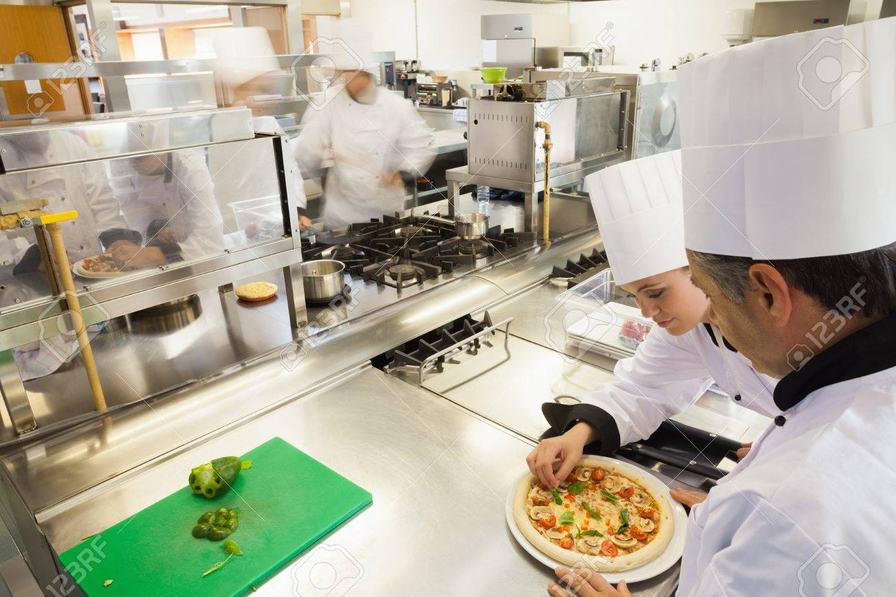 Busy Kitchen cooks preparing pizza in busy kitchen stock photo, picture and