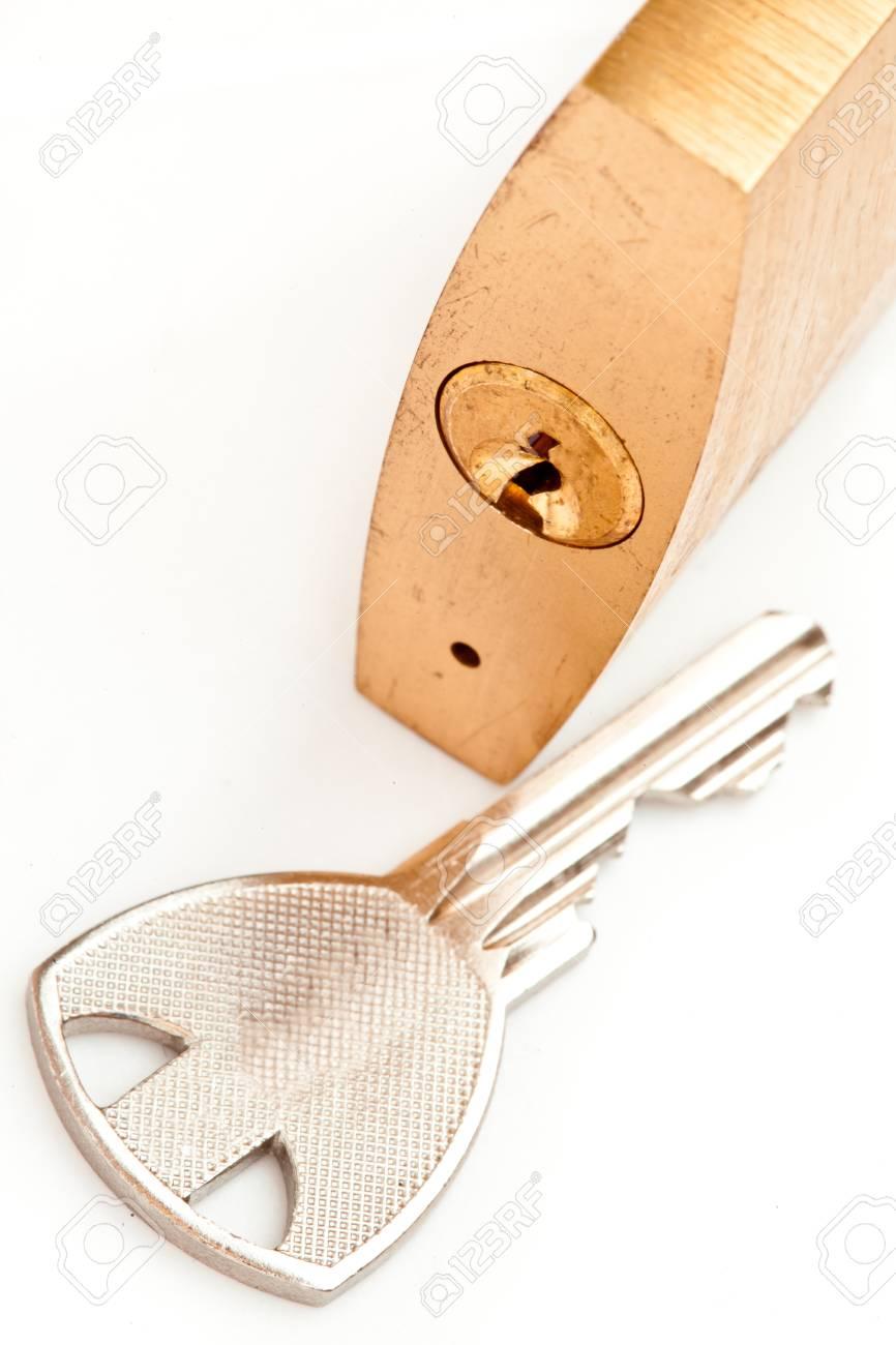 Key lying next to padlock against white background Stock Photo - 16069742