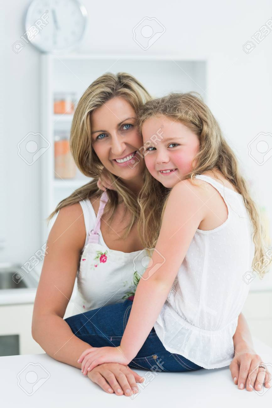 Smiling mother and daughter posing before camera in the kitchen Stock Photo - 16076055