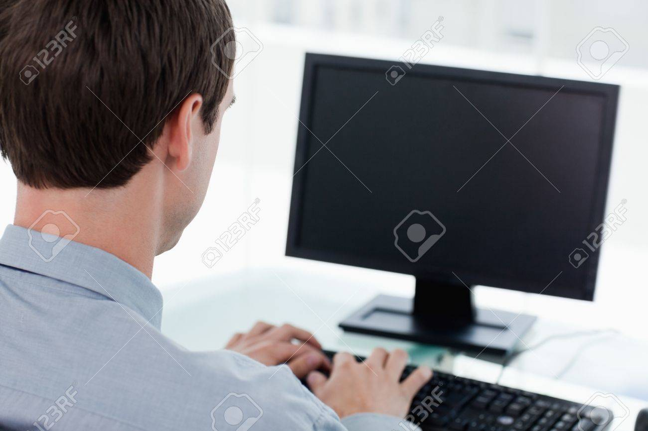 Back view of a businessman working with a computer in his office Stock Photo - 16076302