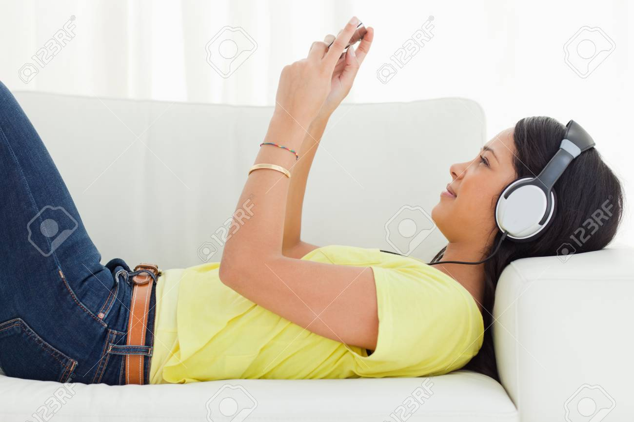 Young Latino woman watching a video with her smartphone while lying on a sofa Stock Photo - 16185449