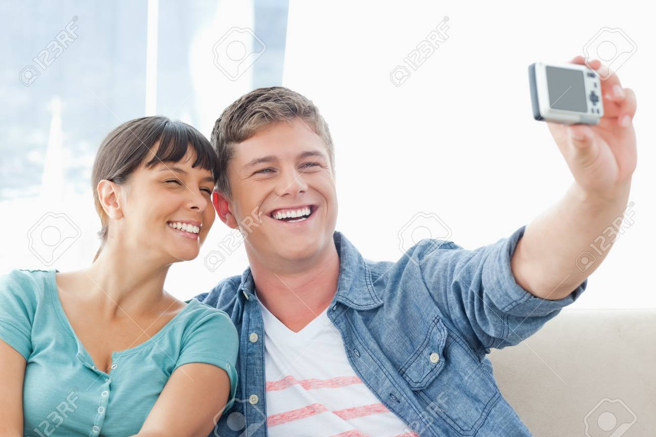 A posing couple sit together on the couch smiling for a photo Stock Photo - 16237690