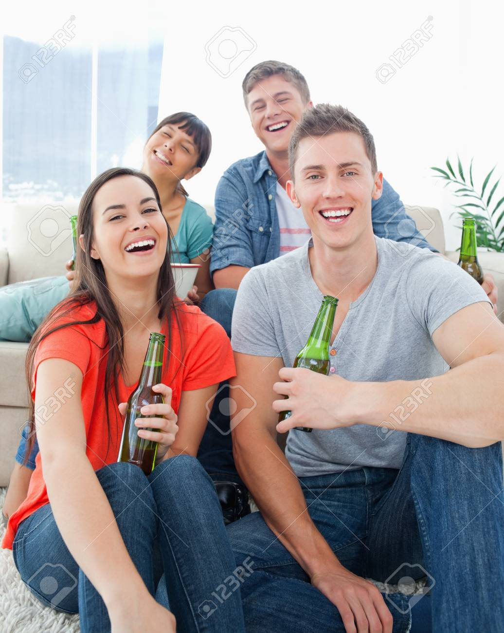A group of friends sitting on the couch and the floor as they hold beers in their hands while laughing Stock Photo - 16237486