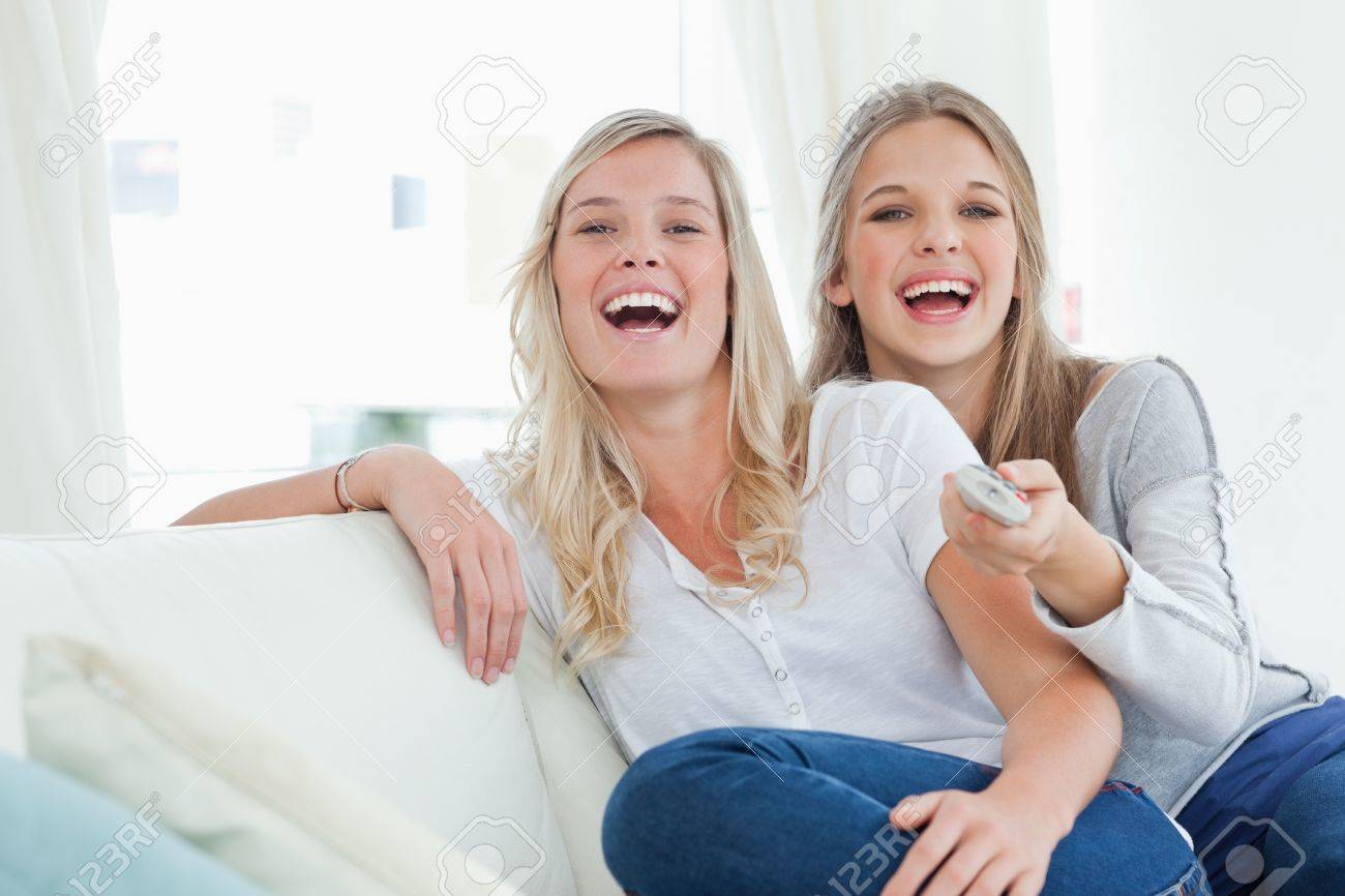 Laughing sisters on the couch as they watch tv and look at the camera Stock Photo - 16235432