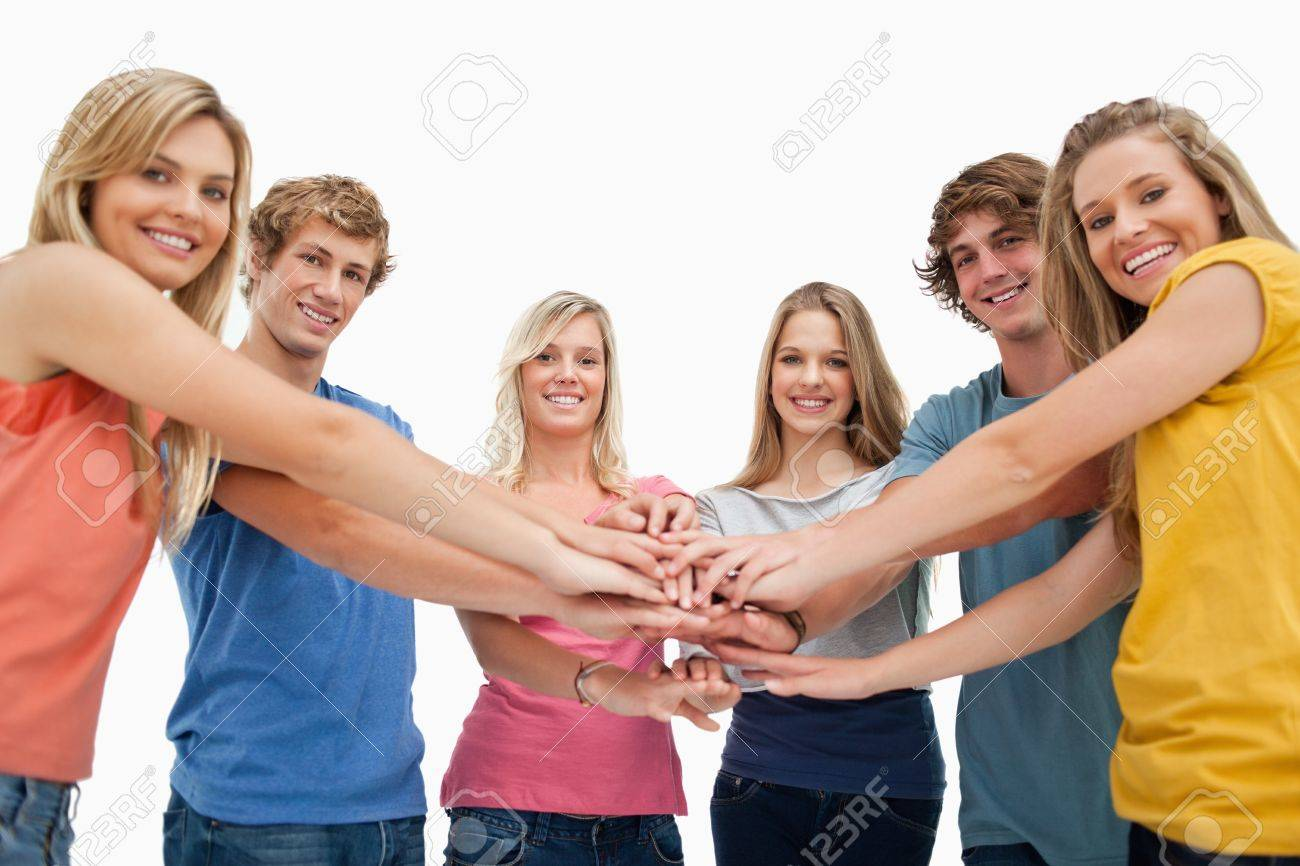 Low angle shot of friends smiling and looking at the camera with their hands stacked in the centre Stock Photo - 16237517