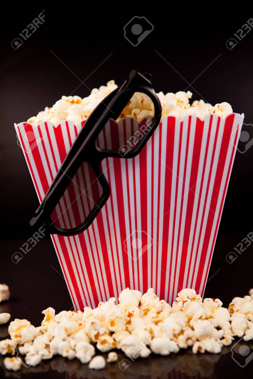 3D glasses hanging on a box full of popcorn against a black background Stock Photo - 16205148