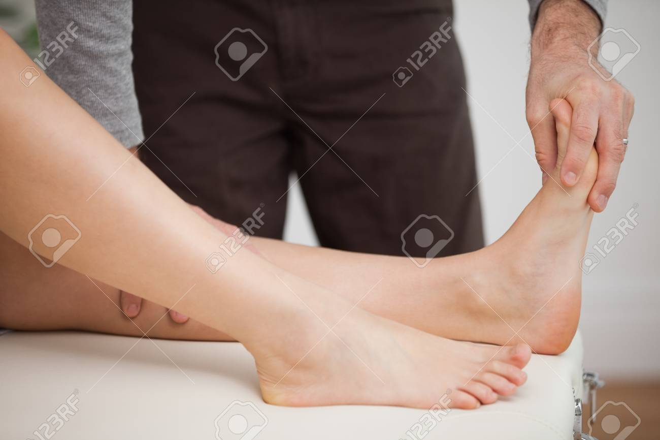 Chiropodist touching the foot of a patient in a room - 16207122