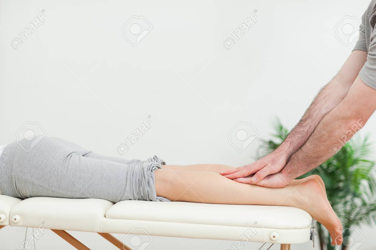 Close up of a masseur massaging the calves of a woman in a room Stock Photo - 16203332