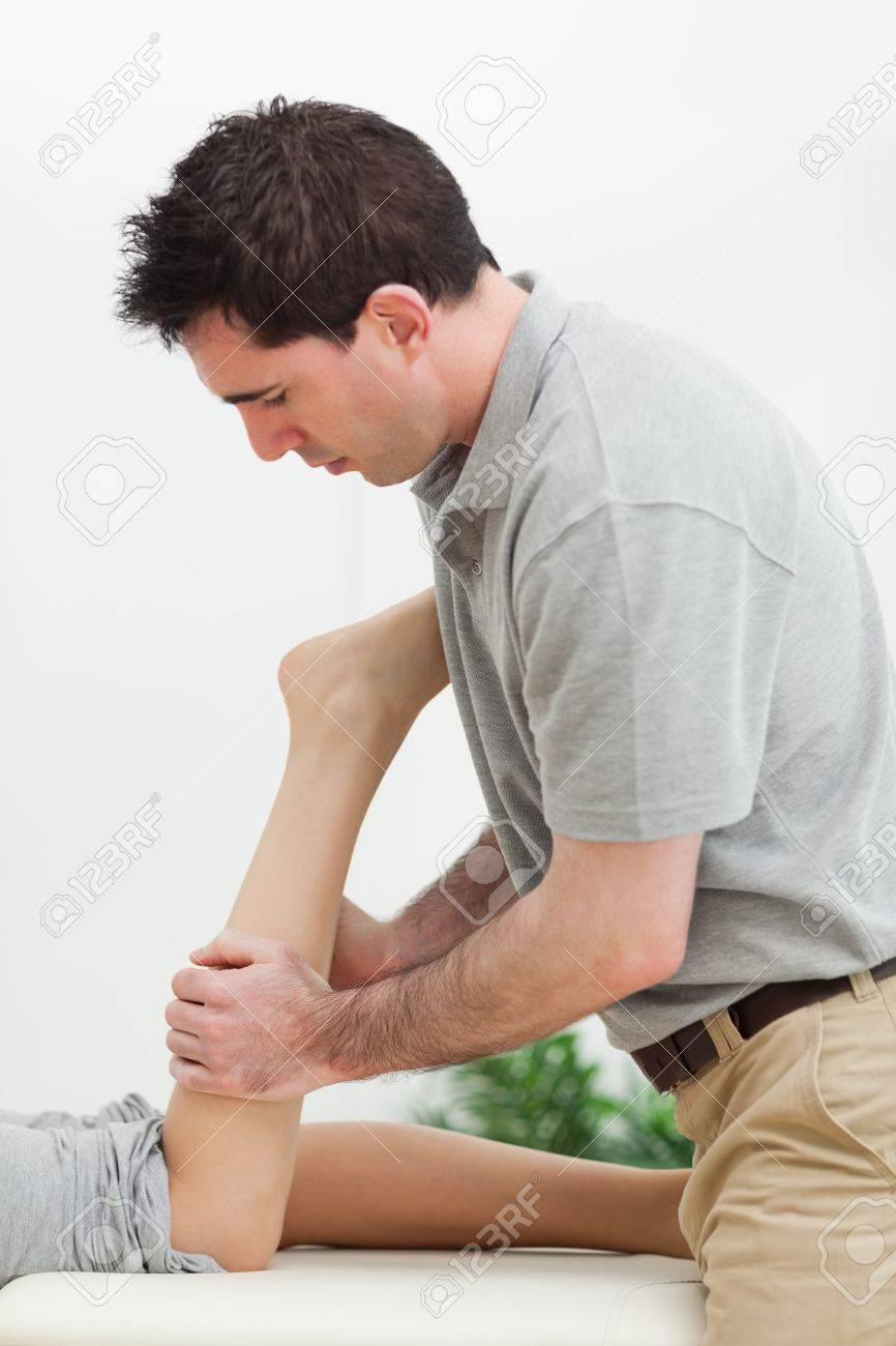 serious masseur massaging the leg of a woman in a room Stock Photo - 16204250