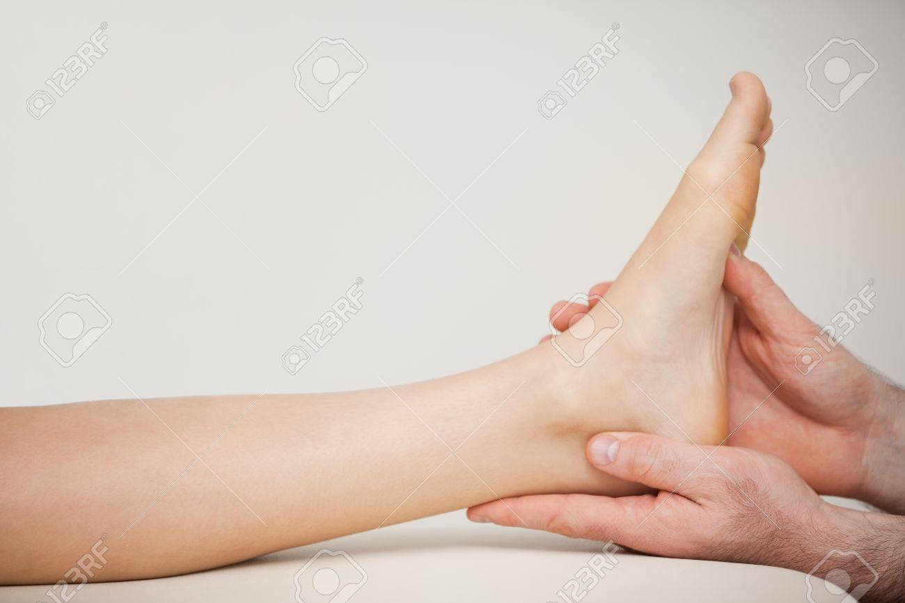 Chiropodist holding the foot of a patient in a medical room Stock Photo - 16202926