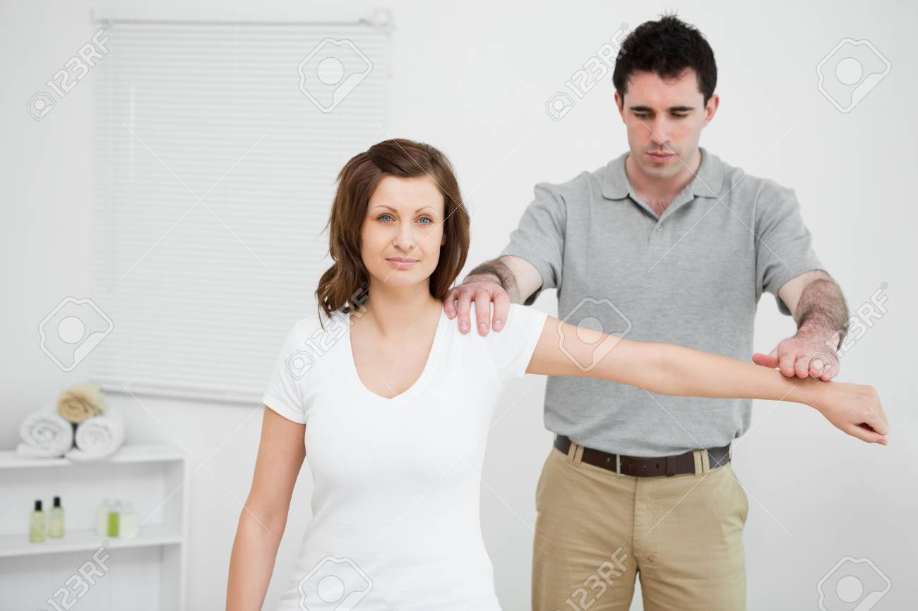 Serious osteopath pressing down the arm of a patient in a medical room Stock Photo - 16204303