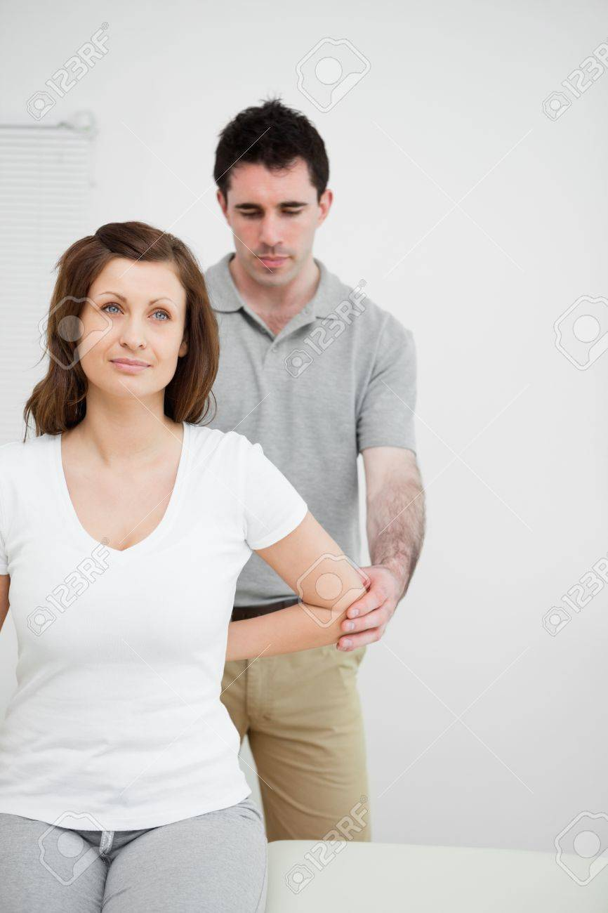 Serious osteopath holding the elbow of a patient in his office Stock Photo - 16204230