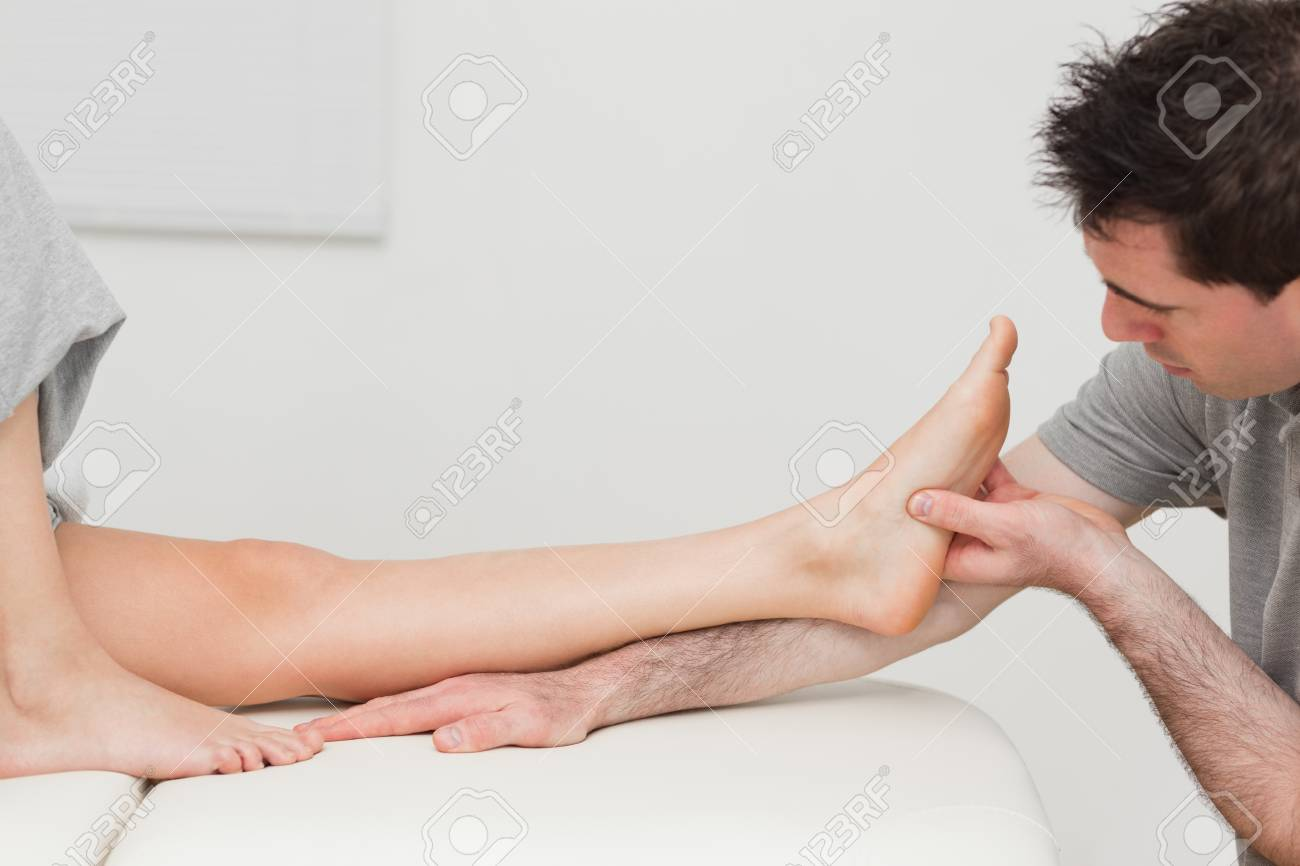 Physiotherapist looking at the foot of a patient in a room Stock Photo - 16204551
