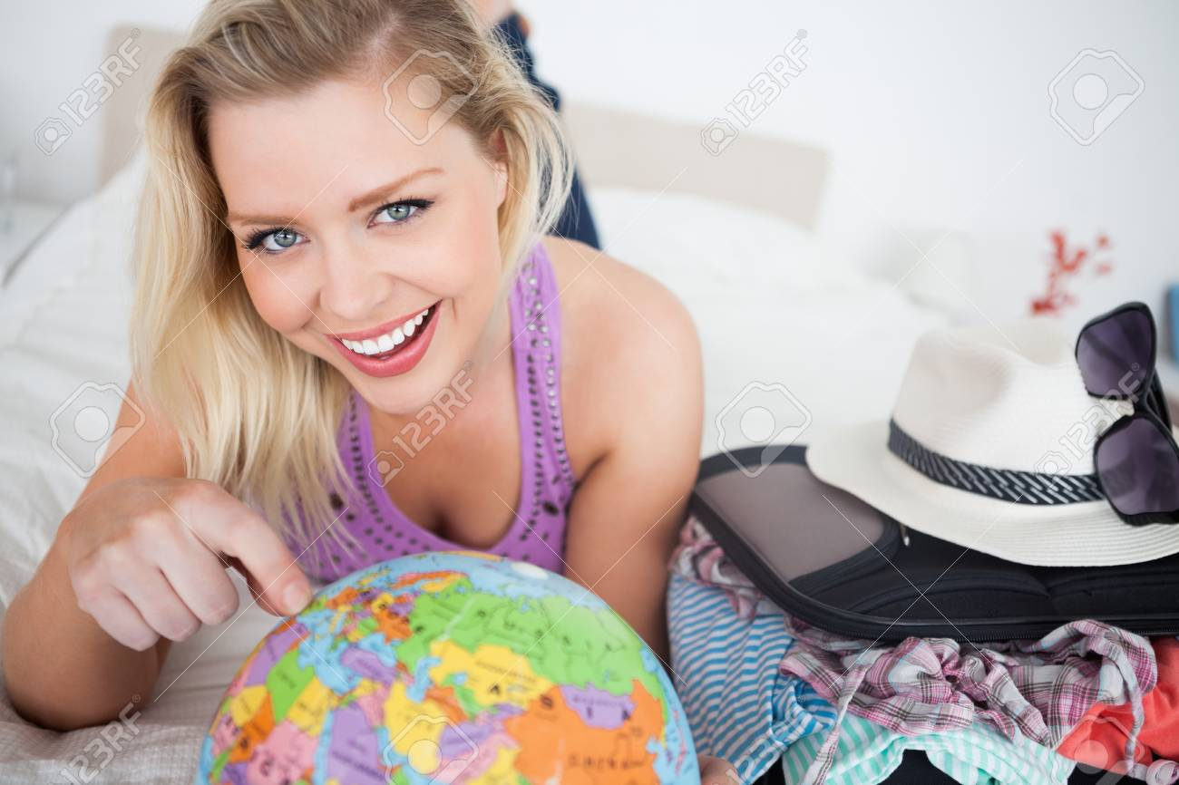 Beautiful woman with a suitcase pointing on a globe while lying on her bed Stock Photo - 16207489