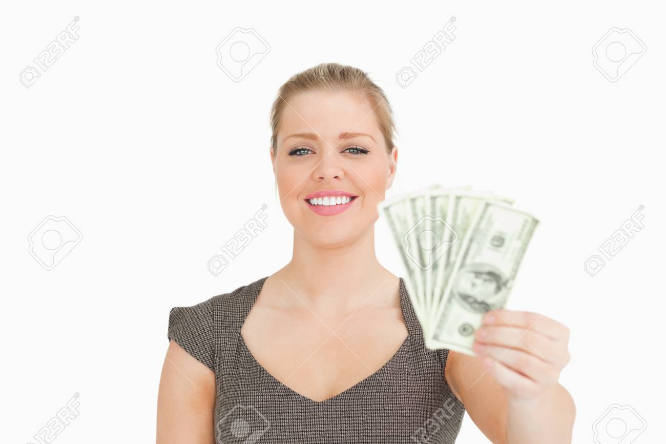 Smiling woman showing dollars banknotes against white background Stock Photo - 16201802