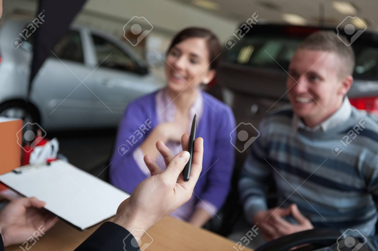 Couple listening to a car dealer in a car shop Stock Photo - 16207114