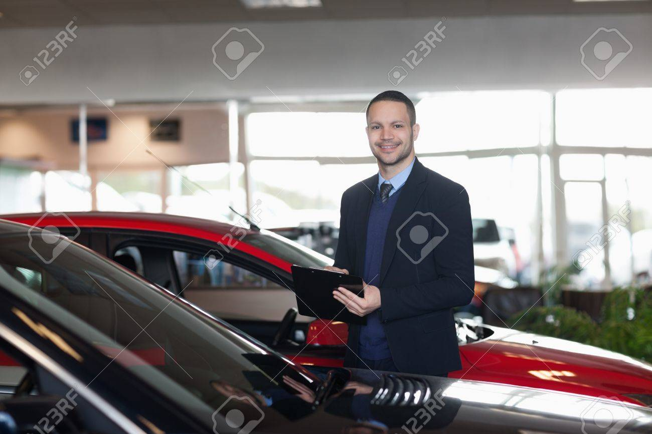Man writing on a notepad beside a car in a garage Stock Photo - 16205172