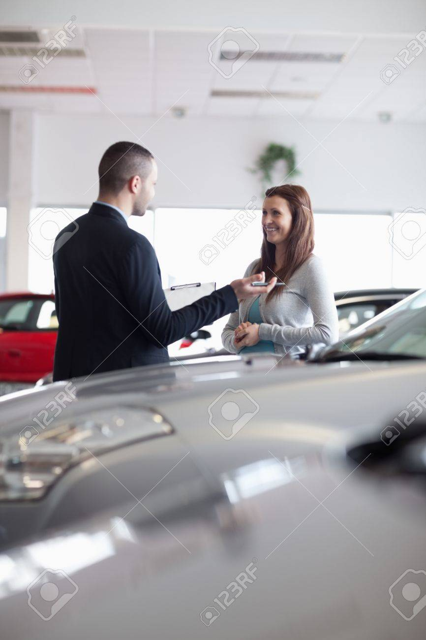 Salesman speaking with a woman in a dealership Stock Photo - 16203589