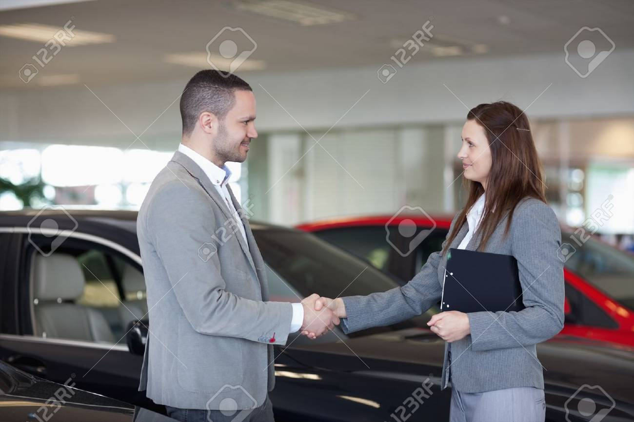 Businesswoman shaking hand of a man in a dealership Stock Photo - 16208211