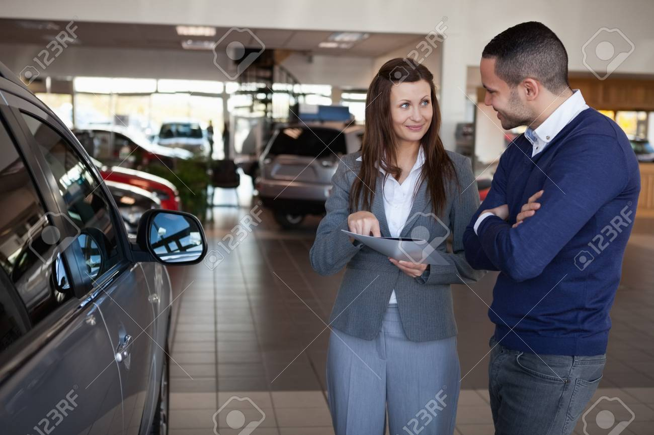 Woman explaining something to a man in a dealership Stock Photo - 16208889