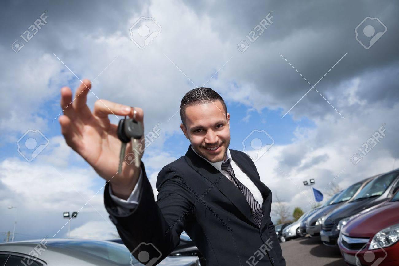 Happy seller holding car keys outdoors Stock Photo - 16204913