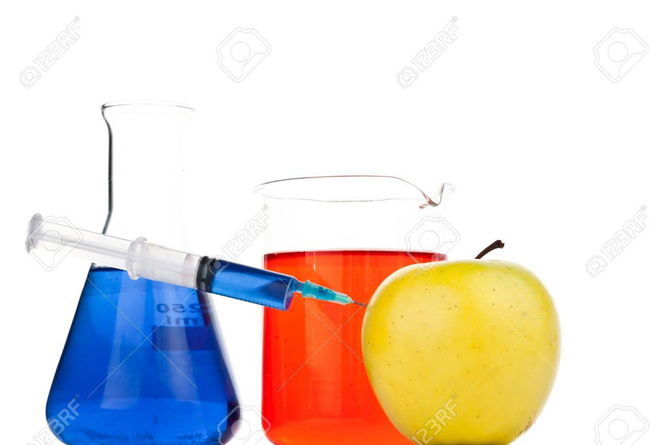 Syringe pricking an apple against a white abckground Stock Photo - 16198620