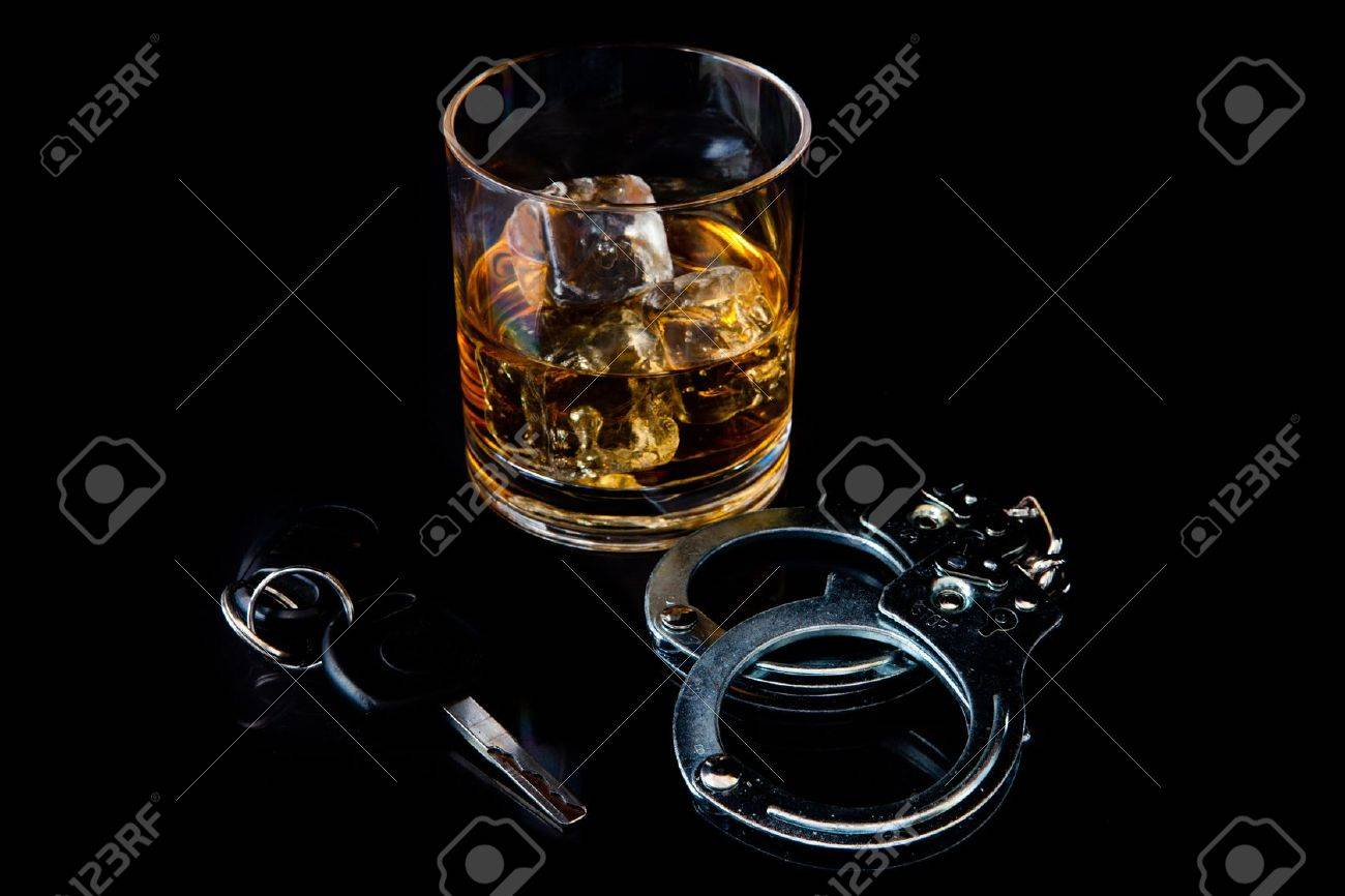 Whiskey on the rocks with handcuff and car key against a black background Stock Photo - 16201656