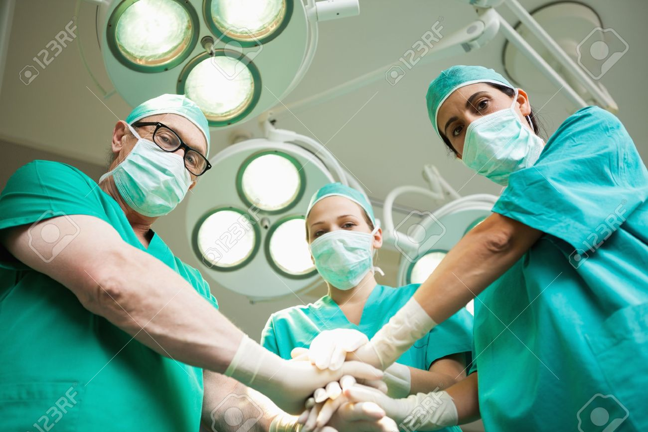 Surgical team joining hands in a surgical room Stock Photo - 16207705