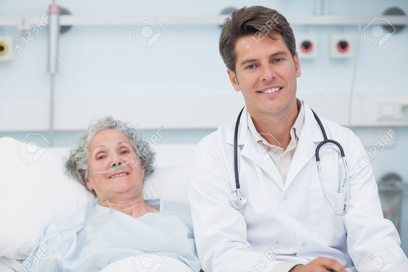Doctor sitting on the bed next to a patient in hospital ward Stock Photo - 16203089