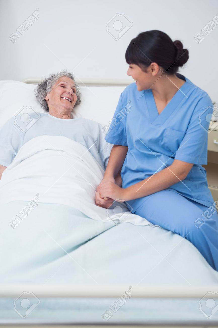 Nurse sitting on the medical bed next to a patient in hospital ward Stock Photo - 16203166